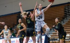 Hoop Dreams: Washburn's junior guard Nuria Barrientos fighting through the Lions defense for the easy two points. Barrientos had a total of 12 points during the game against the lions.