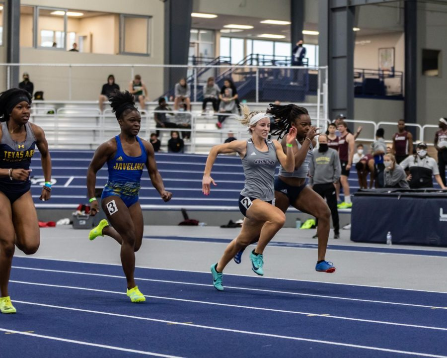 Neck and Neck: Washburn's Isabella Hohl and Mandana Vouillemin running side by side in the 60-meter dash. Hohl finished in 16th place with a time of 7.88 seconds, and Vouillemin placed 18th with a time of 7.90 seconds.