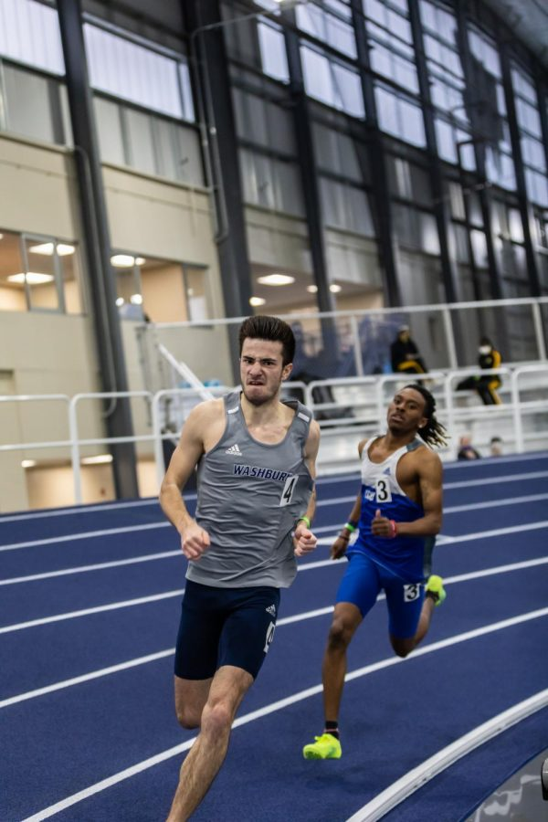 Run to Achieve: Washburn's Romain Henry running around the bank toward the home stretch of the 400 meter. Henry finished the race in 7th place with a time of 48.92 seconds.