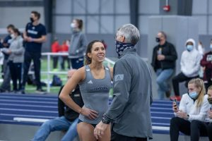 Run fast, vault high: Washburn's senior pole vaulter Virgi Scardanza talking with assistant coach Rick Attig after a great vault. She always gives 100% each time she pole vaults.