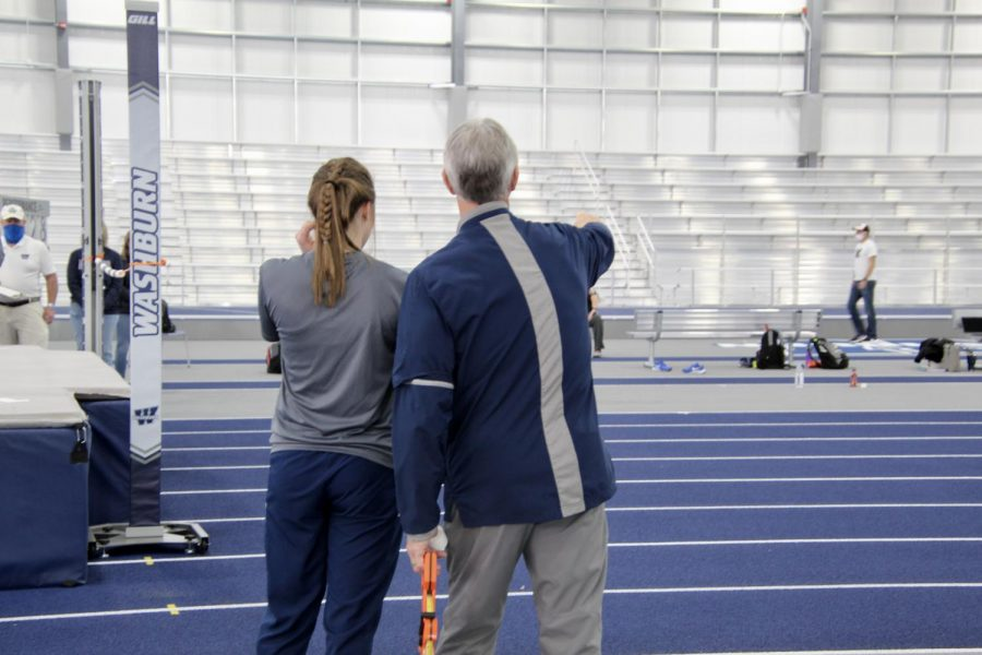 A teaching moment: Taylor Grasser is seen talking to Coach Attig while warming up for her first event. Grasser placed 11th in high jump at a height of 1.34 meters.