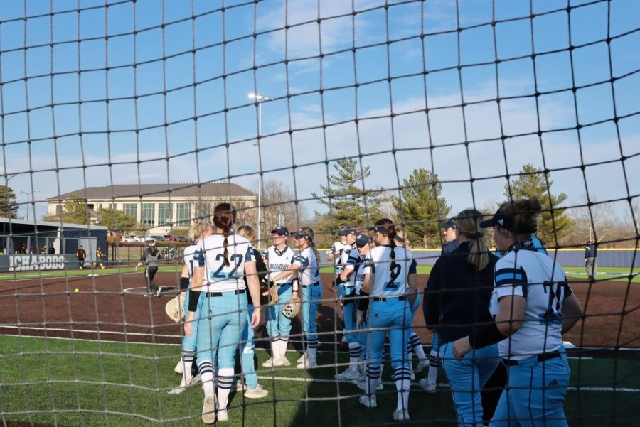 1,2,3 break!: The team gathers to prepare to bat after finishing an inning on the field.