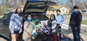Putting words into action: Dr. Park and four of his students unload diapers at Community Action at the end of their Diaper Drive. Their efforts will help several needy families in Shawnee County this year.