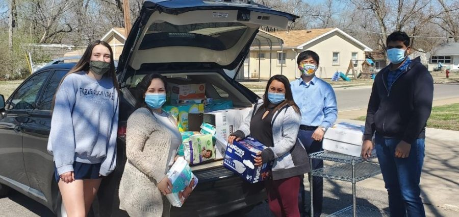 Putting words into action: Dr. Park and one of his students unload diapers at Community Action at the end of their Diaper Drive. Their efforts will help several needy families in Shawnee County this year.