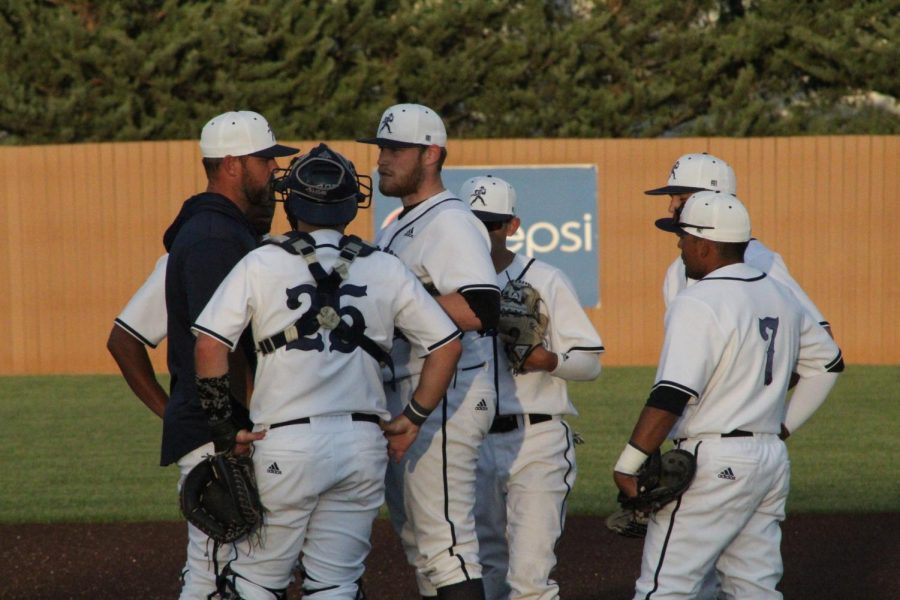 Keep composure: The team gathers around senior starting pitcher Sean McElwee in the sixth inning of Washburn's win over Emporia State on 4/10.