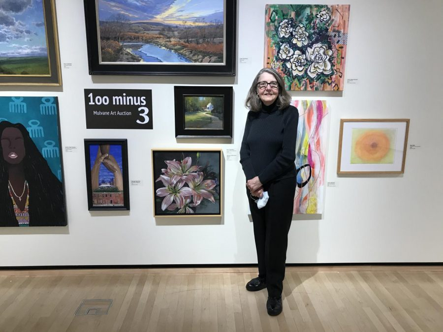 100 Minus 3: Barbara Waterman-Peters stands by her artwork which she titled Lilies. Art pieces submitted by other artists are arranged behind her as well in the Rita Blitt Art Gallery.