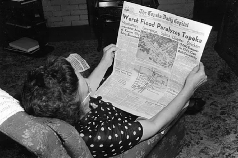 """Bad news: A woman is shown reading """"The Topeka Daily Capital"""" with a horrifying title that reads,"""