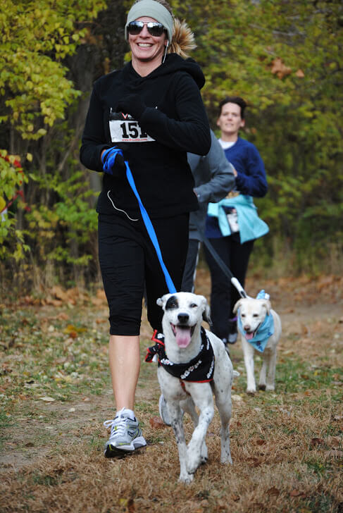 Two runners and their dogs.