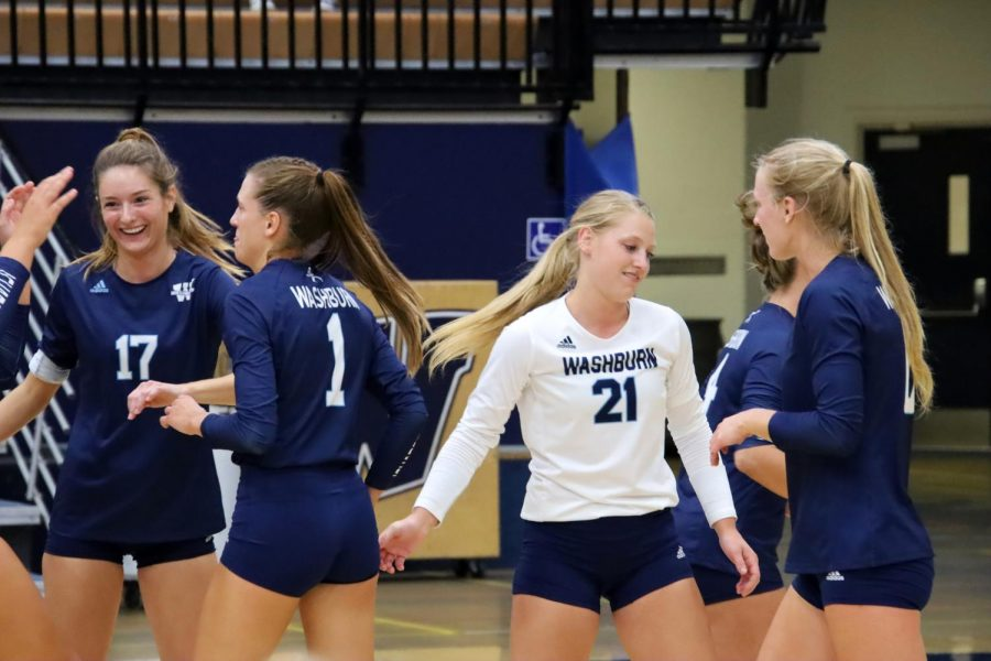We did it: The team celebrates after earning a point. Madison Johnson(17) and Faith Rottinghaus(21) congratulate their teammates in a volley well done.